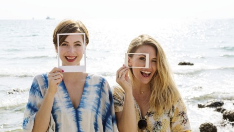 Two women at the beach hold photos of their faces in front of their faces