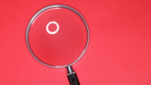 Magnifying glass on pink background