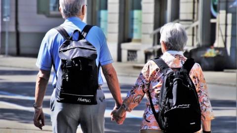 Senior couple holding hands walk down the street