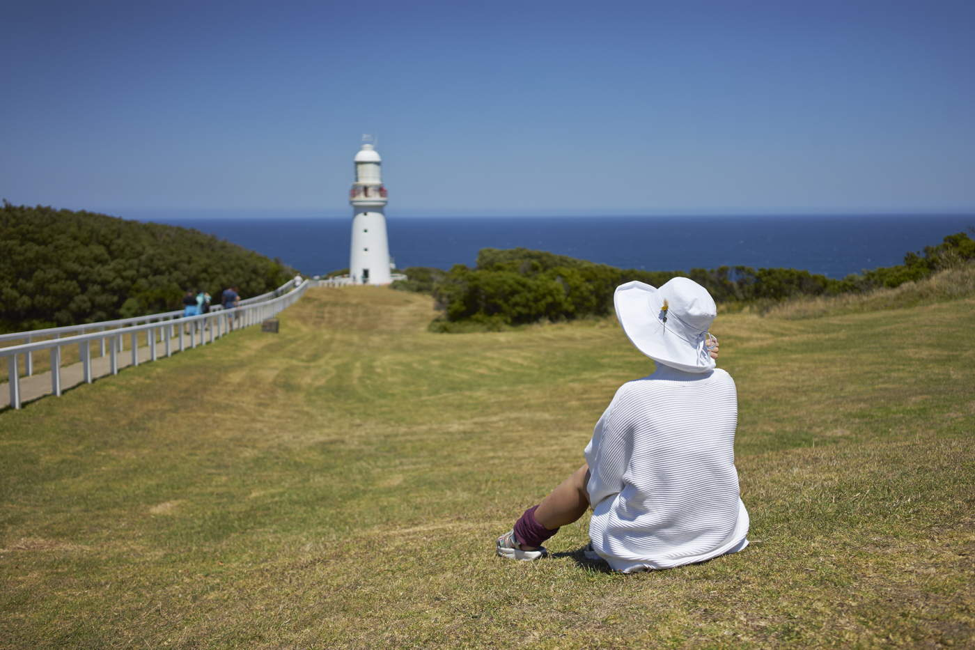 young lady sitting on grassland looking at lighthouse