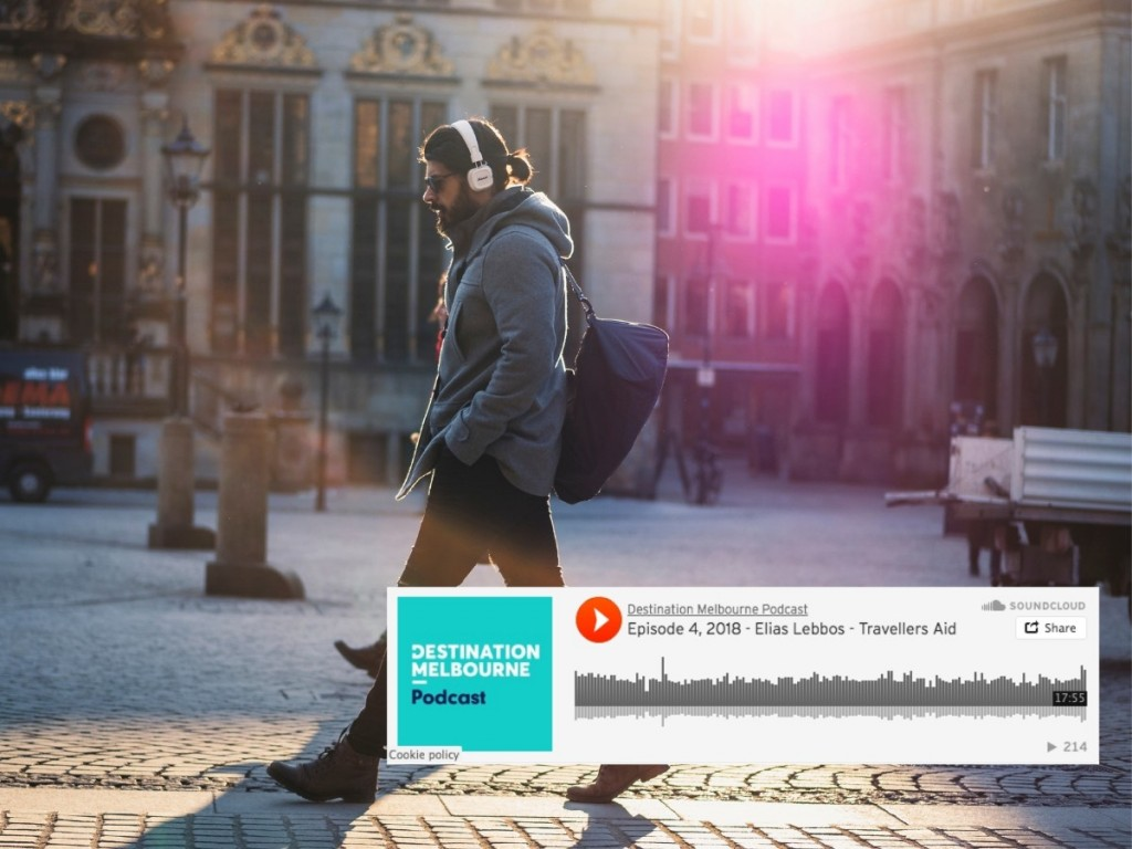 Photo of man walking in city with headphone on